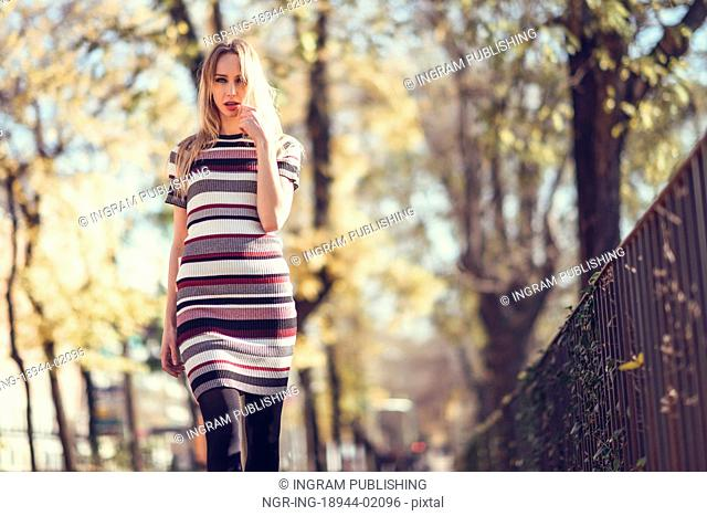 Young blonde woman walking in the street. Beautiful girl in urban background wearing striped dress and black tights. Female with straight hair