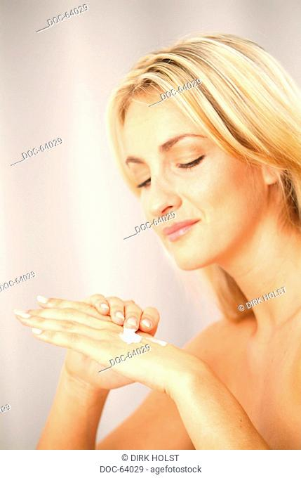 portrait of young woman - put skin creme onto her hands