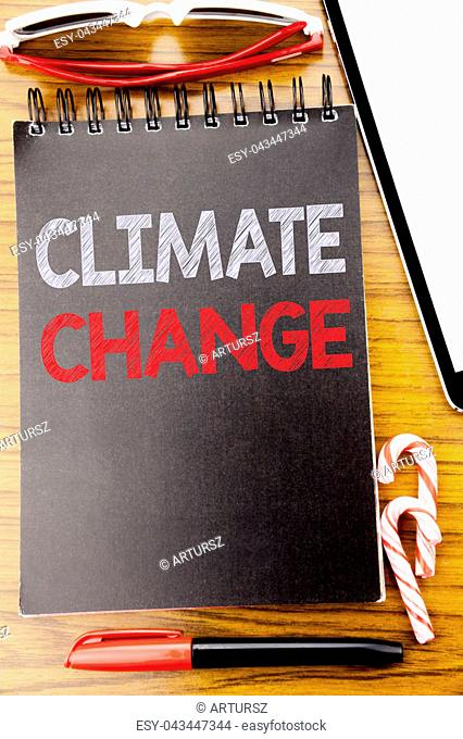 Word, writing Climate Change. Business concept for Global Planet Warming Written on notebook book, wooden background with sticky sunglasses and red pen