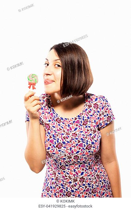 happy girl in pink dress trying to lick a spiral lollipop