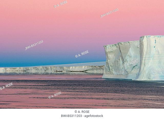 red morning sky over the edge of a table iceberg near the iceberg resting place Austasen, Antarctica