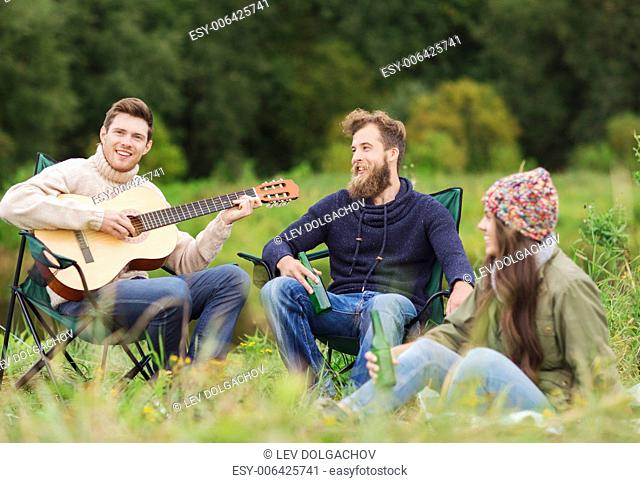 adventure, travel, tourism and people concept - group of smiling tourists playing guitar and drinking beer in camping