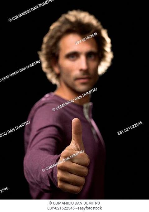 man in purple shirt gesture ok in focus