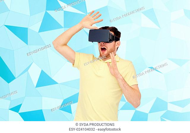 3d technology, virtual reality, entertainment and people concept - scared young man with virtual reality headset or 3d glasses playing game over low poly...