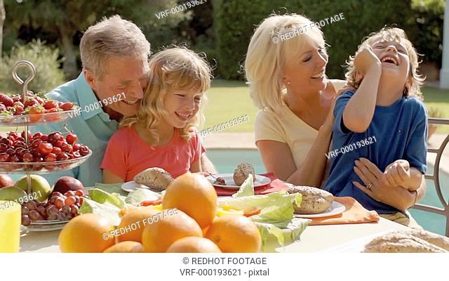 Grandparents and grandchildren playing and sitting at table of food in garden