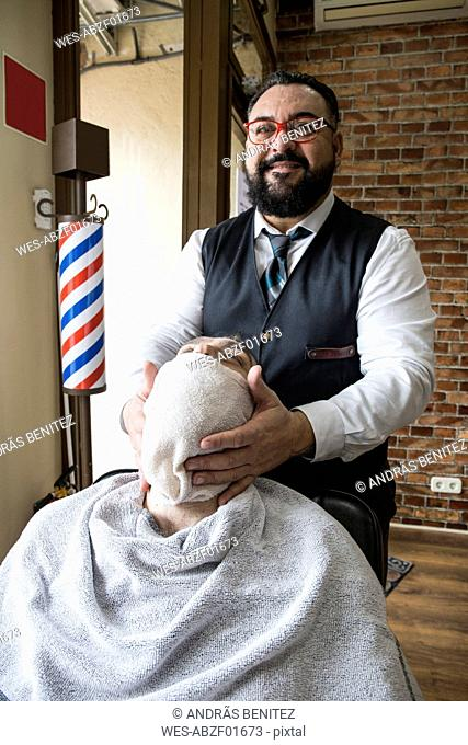Barber putting a towel on a man's beard after shaving