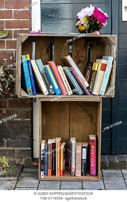 Tilburg, Netherlands. Free books inside wooden fruit crates, parked outside in the streets, for pedestrians to take home for free to read