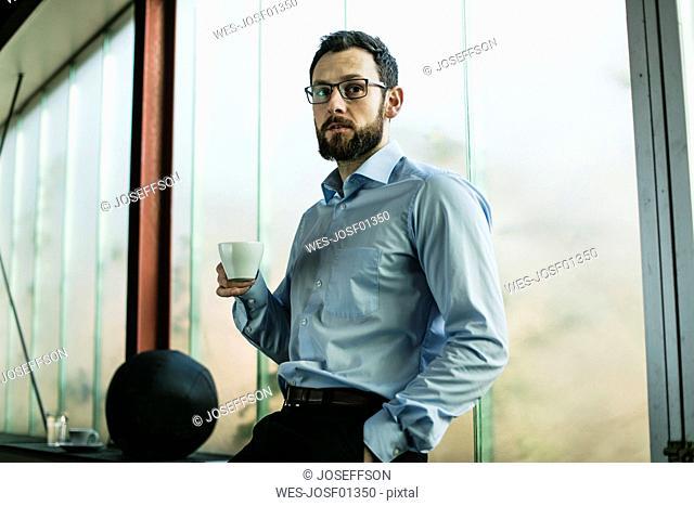 Businessman in office drinking coffee