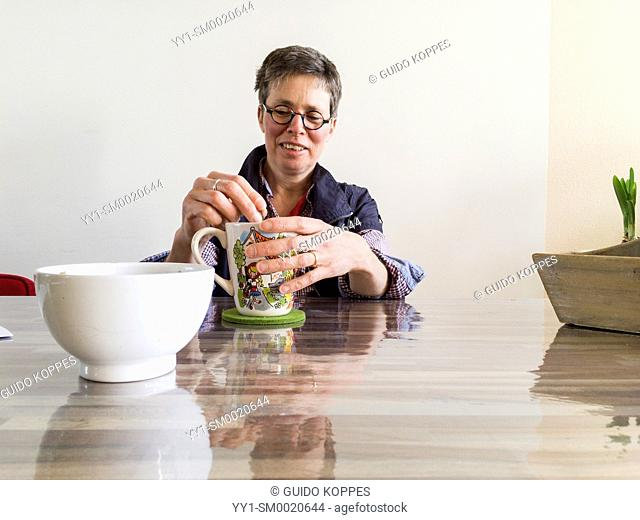 Tilburg, Netherlands. Mid adult caucasian woman, having multiple sclerosis or MS for over a decade, dealing with her disease by taking in healthy liquids and...