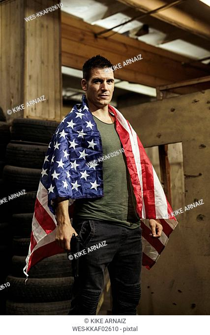 Portrait of man wearing American flag holding a gun