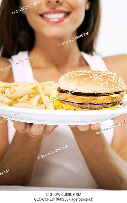 Woman holding a plate of hamburger and fries