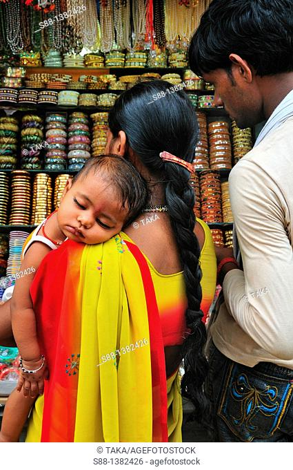 Pilgrim family shopping at the shop by the Ganges River in the Holly town
