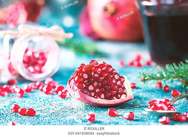 Piece of ripe pomegranate fruit with fir tree branches on blue vintage background
