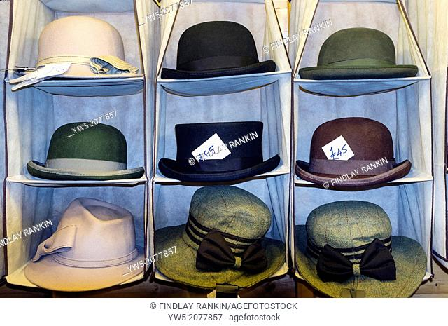 Selection of mens' and womens' hat for sale and on display in a clothing hanger, Glagow, Scotland, Great Britain, UK