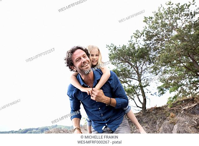 Father carrying happy daughter piggyback