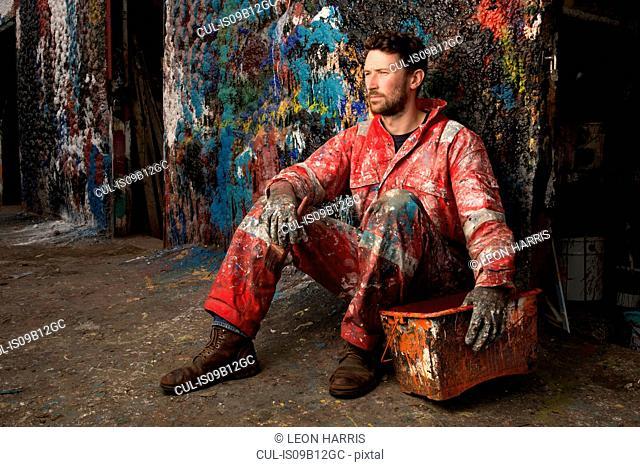 Portrait of male ship painter sitting against paint splattered wall