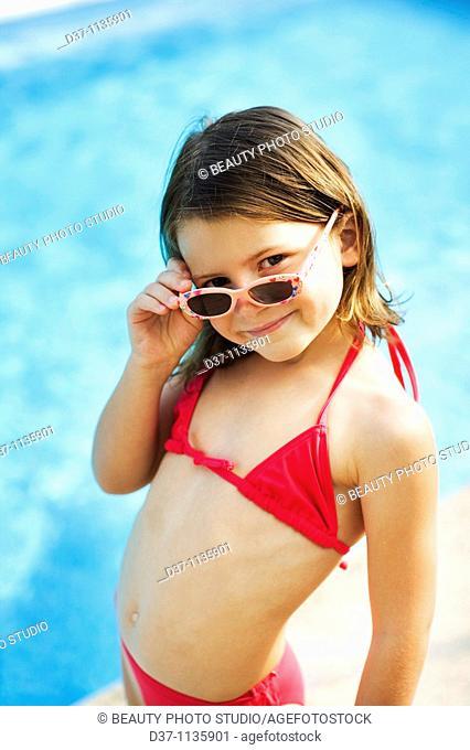 Young girl in bikini, looking over sunglasses