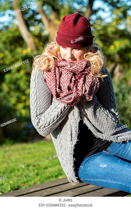 attractive blond woman in the park is glad about the autumn