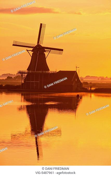 Windmill reflected in a canal during sunrise in the small town of Zaanse Schans, Holland, Netherlands, Europe. - ZAANSE SCHANS, HOLLAND, NETHERLANDS, 15/07/2014