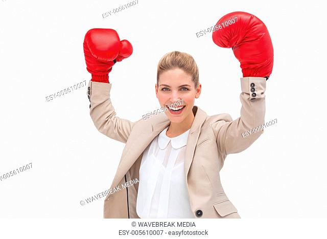 Cheering businesswoman wearing boxing gloves