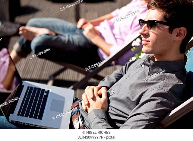 Two men relaxing on deck chairs with a laptop