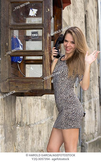 Sexy and elegant Ukrainian woman wearing a leopard-skin print suit posing reclining to a telephone booth and talking on the phone for a photographic sequence in...