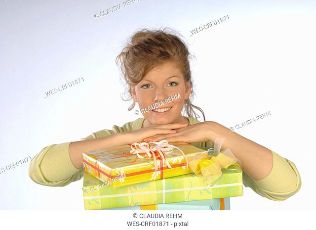 Young woman smiling with head in hand on gift packages, portrait