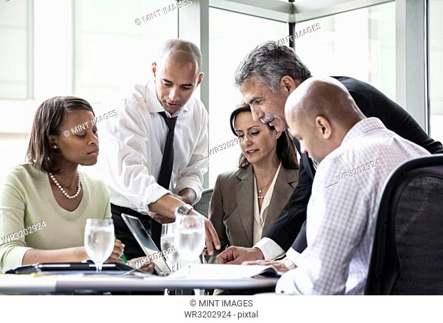 A mixed race group of male and female business people in a meeting at a conference table next to a large window in a convention centre