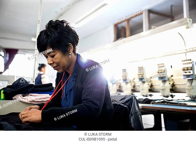 Female factory worker removing stitches from black cloth from speed stitching programmed embroidery machine in clothing factory