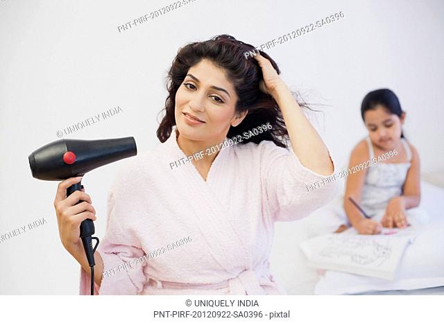Woman drying her hair with her daughter studying in the background