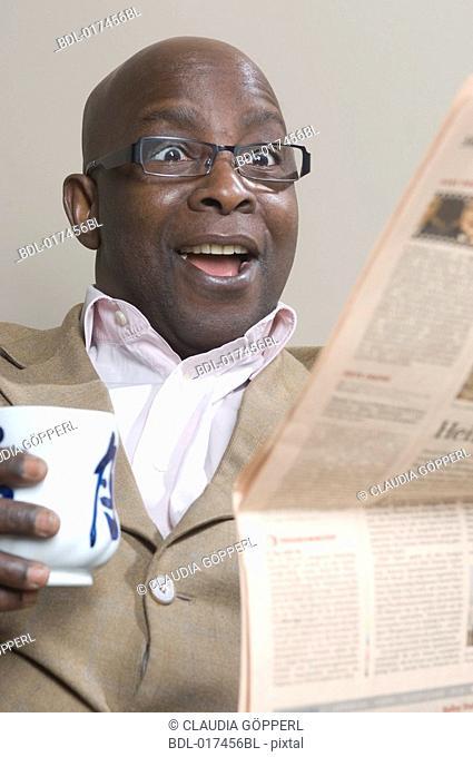 black businessman reading newspaper looking astonished