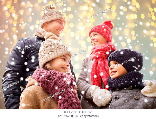 family, christmas, winter, season and people concept - happy family outdoors over holidays lights background and snow