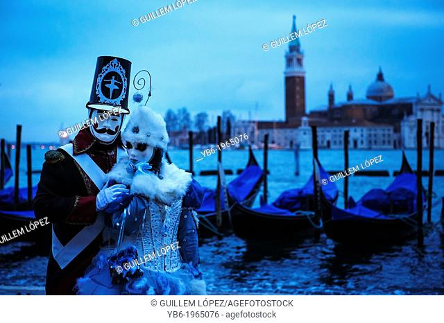 Carnival of Venice participants posing with their costumes at Venice's waterfront, Italy