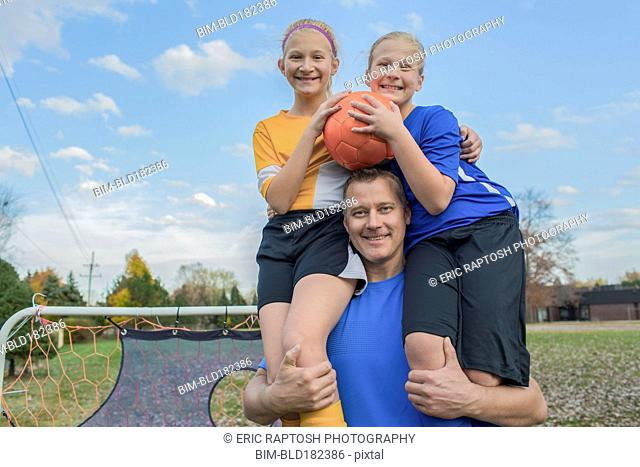 Caucasian father holding daughters in field