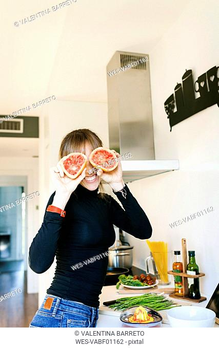 Young woman squeezing grapefruit juice