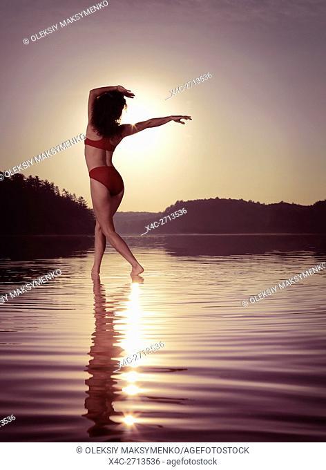 Young woman in swimsuit dancing in the sun on the water in beautiful morning sunrise scenery. Muskoka, Ontario, Canada