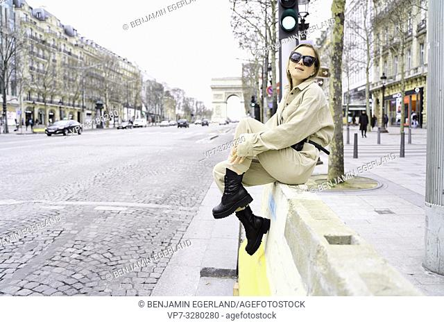 fashionable woman at street during fashion week, Arc de Triomphe in background, in Paris, France
