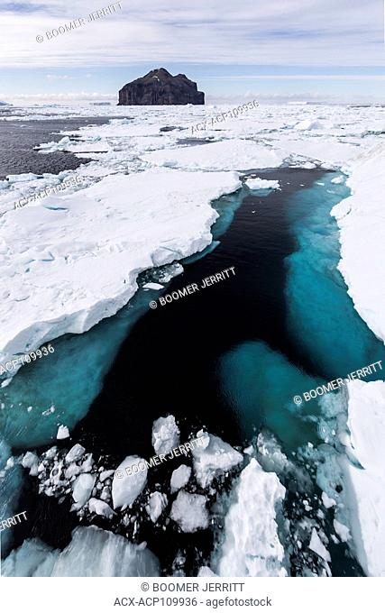 An open lead in drift ice created by wind and current leads to an island in the Weddell Sea. Antarctica