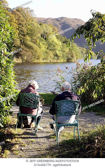 UK, England, Cumbria, The Lake District, Grasmere, Keswick Road, Waterside Hotel, The Lake at Grasmere, chairs, senior couple
