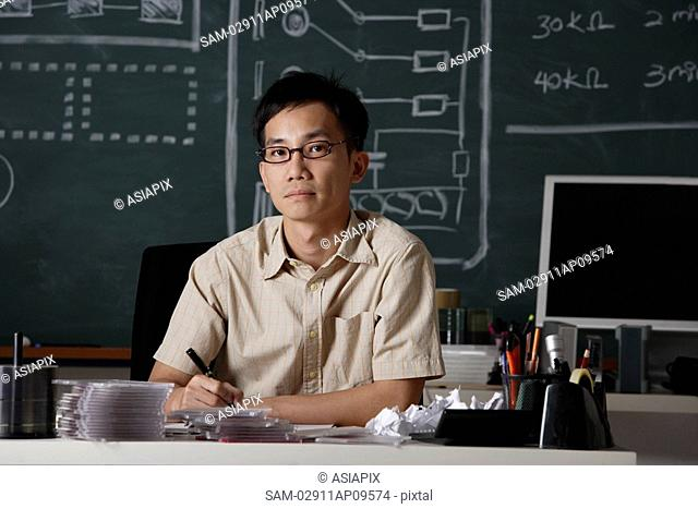man sitting at desk in front of chalk board