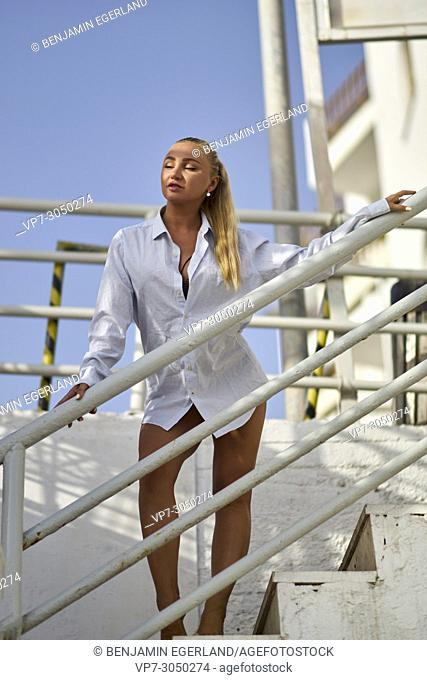 sensual woman in business shirt enjoying summer breathe while standing on stairs next to the beach. Russian ethnicity. In holiday destination Hersonissos, Crete