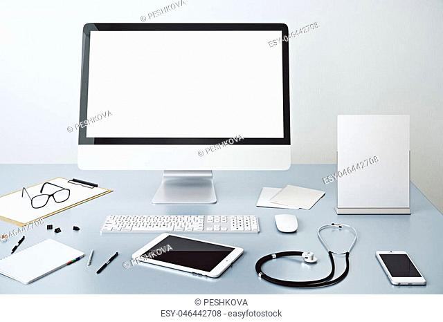 Close up of doctor's workplace with empty white computer monitor, other devices, paperwork and stethoscope. Mock up, 3D Rendering
