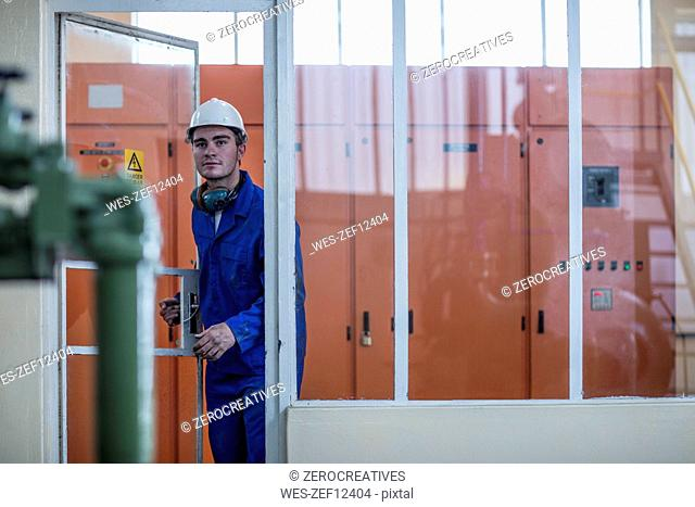 Worker leaving technical room in factory