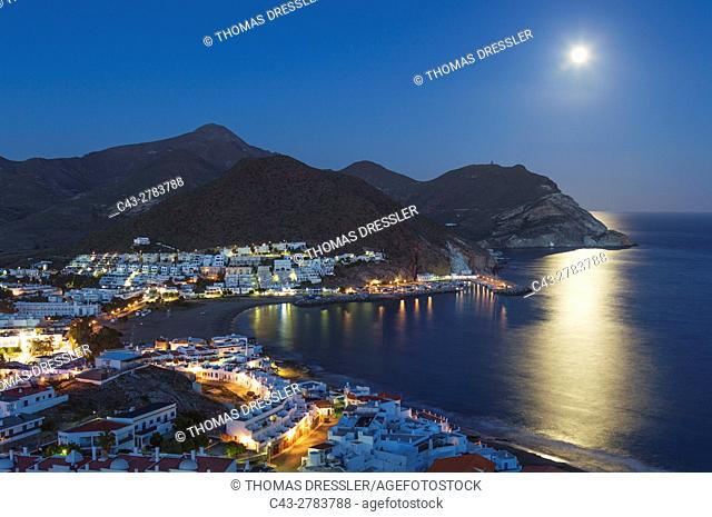 The seaside town of San Jose in the nature reserve Cabo de Gata-Nijar. With full moon at dusk. Almeria province, Andalusia, Spain