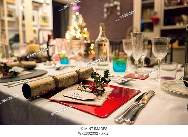 A table laid for a Christmas meal, with silver and crystal glasses and a Christmas tree in the background