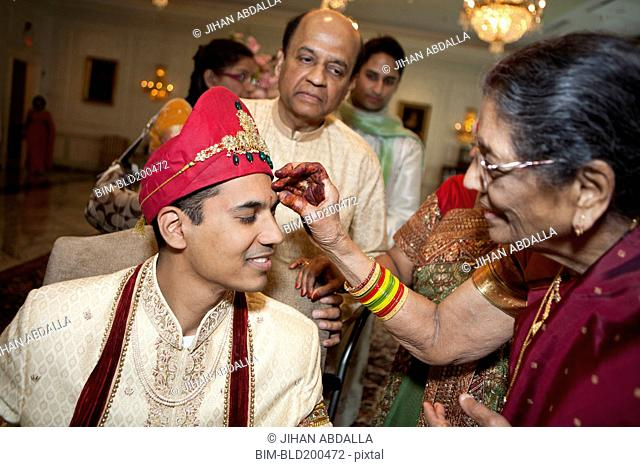 Indian woman marking groom's face