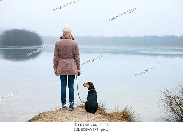 Rear view of woman with dog looking out from riverbank