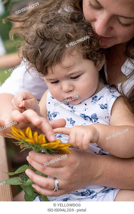 Mother and daughter looking at flower together