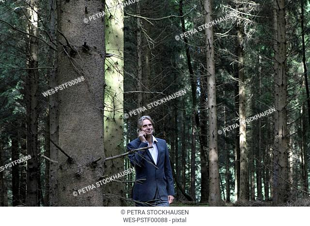 Businessman on cell phone in forest