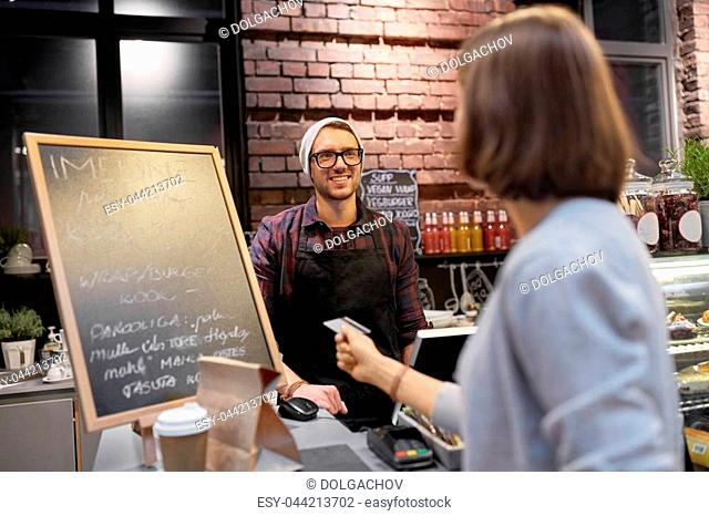 small business, payment, people and service concept - happy barman and woman paying with credit card at cafe